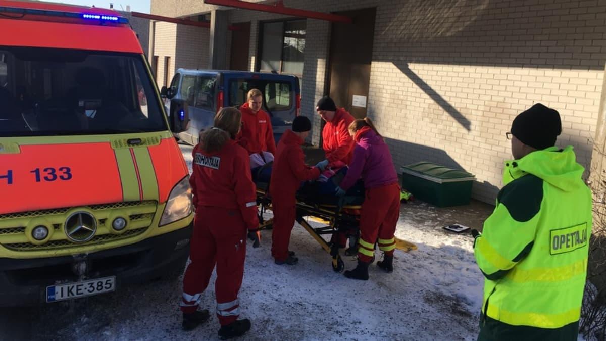 Potilasta viedään ambulanssiin.