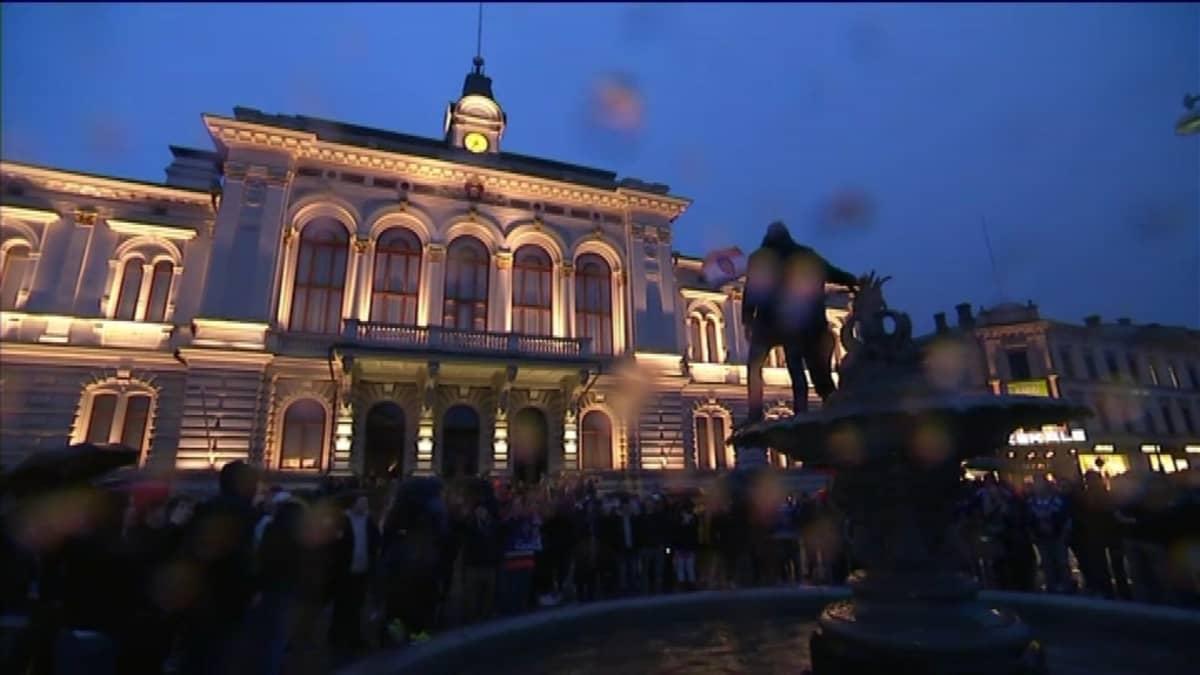 Tamperee valaistu raatihuone taustalla, juhlijoita suihkulähteen päällä etualalla.