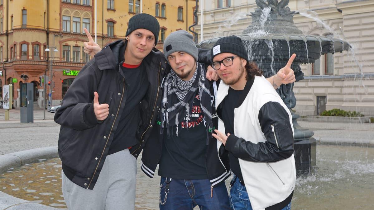 Rap-yhtye mansesterin jäsenet poseeraavat Tampereen keskustorilla suihkulähteen edessä.