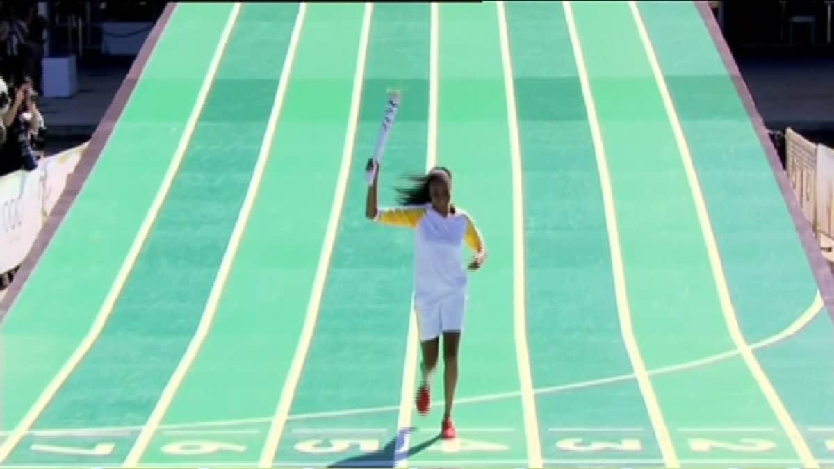 Pitkä tumma nainen vaaleassa urheiluasussa ottaa juoksuaskelia olympiasoihtu oikeassa kädessään alaspäin laskeutuvalla vihreällä juoksualustalla.