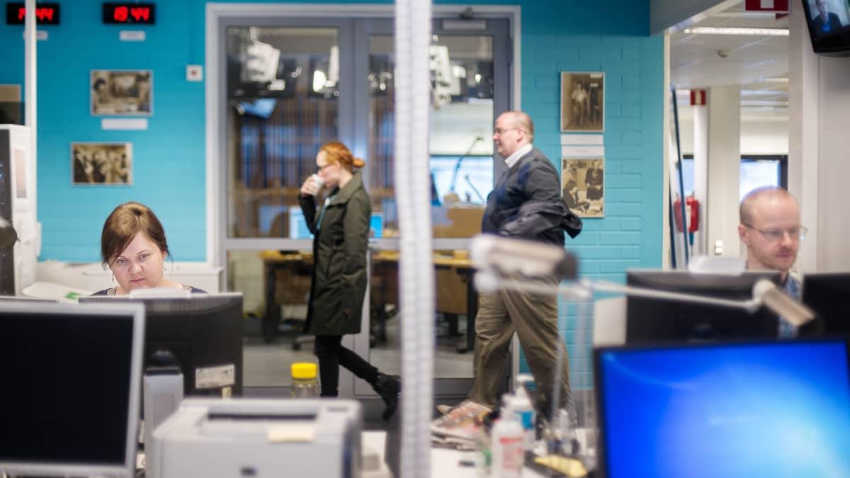 Näkymä Yleisradion radiouutisten toimitukseen maaliskuussa 2015. Edessä vasemmalla Monna Tervo ja oikealla Markus Myllyoja. Radiouutisten kuuluttamo näkyy lasiovien takaa.