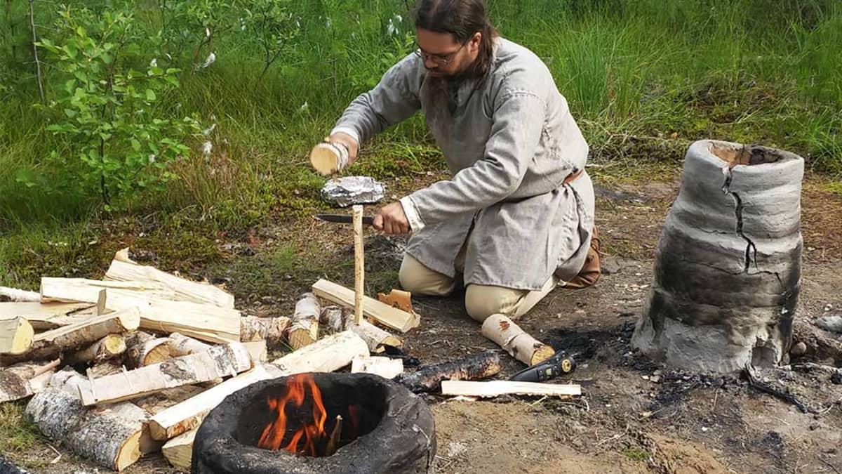 Joni Karjalainen valmistautuu sulattamaan rautamalmia savimasuunissa Kierikin muinaiskylässä 30.7.2016.