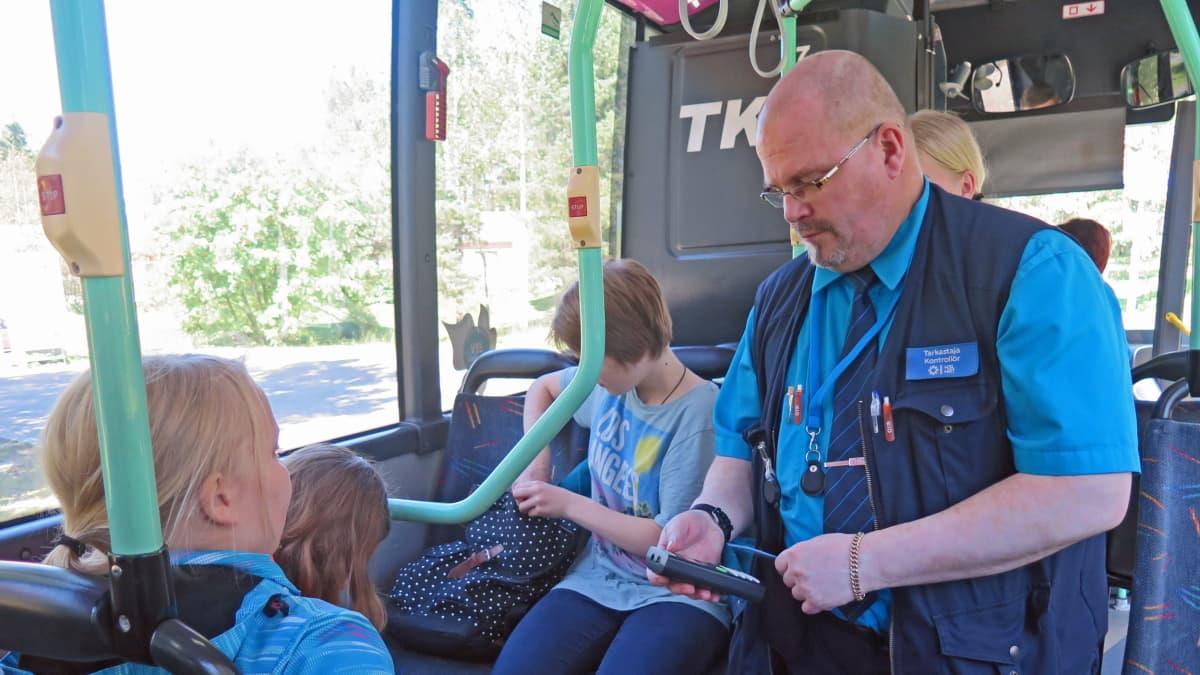 Tarkastaja tarkastaa lippua bussissa