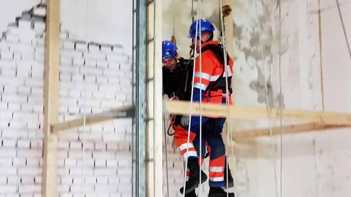 Tuulivoimalan pelastustumisharjoituksessa harjoitellaan myös työkaverin pelastamista kiipeilyköysien avulla. Toni Aikio tuo Jani Lahtea alas Oulun kiipeilykeskuksen harjoitustornista.