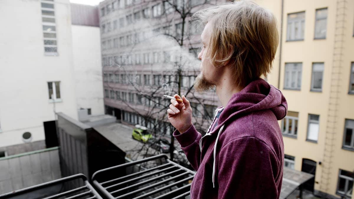 Mies polttaa tupakkaa parvekkeella.