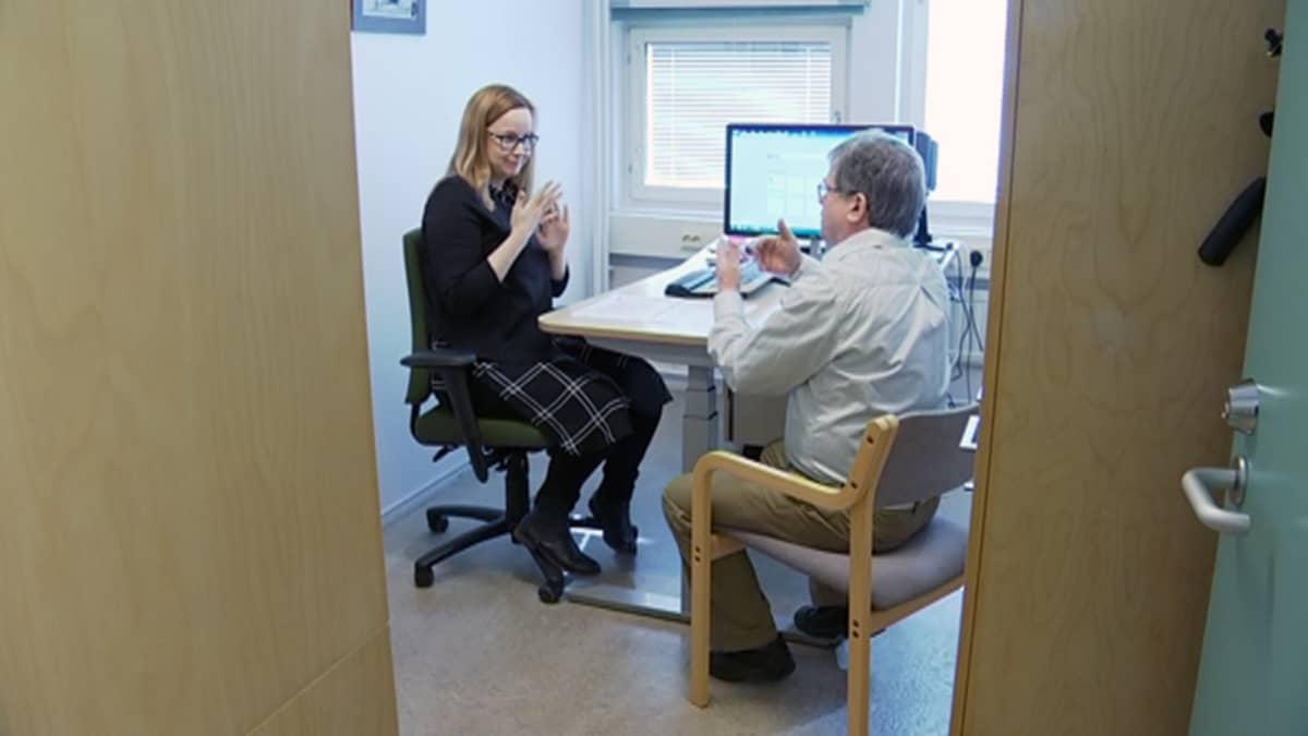 Viittomakielinen työvalmentaja ja asiakas keskustelemassa toimistossa.