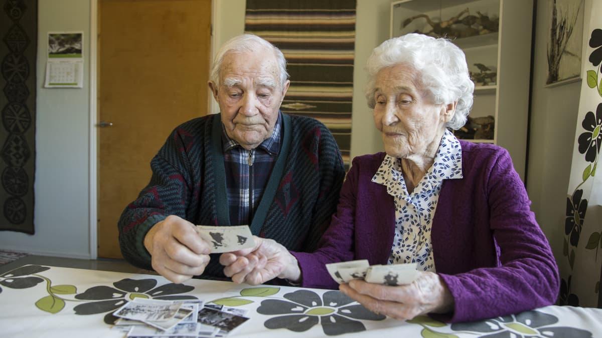 Raili ja Veikko Punakallio katselevat vanhoja valokuvia kotonaan Heinolan Lusissa.