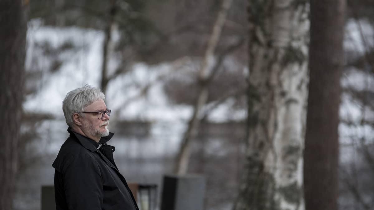 Mies seisoo hautausmaalla