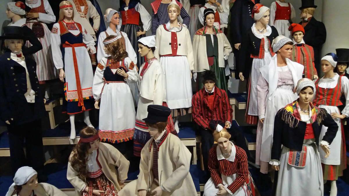 Mallinukkejen päällä iso kirjo kansallispukuja Suomen käsityön museossa Jyväskylässä.