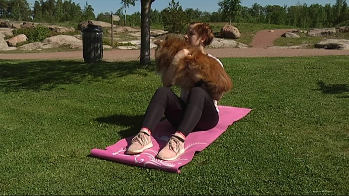 Nainen istuu maassa koira sylissään