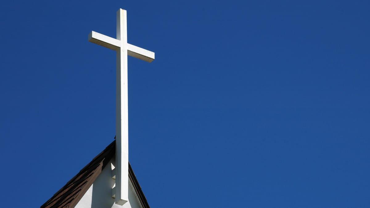 Valkoinen risti kirkon katolla sinitaivasta vasten