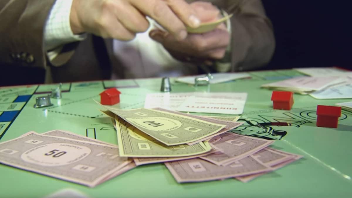 Monopolin pelilauta, henkilö lyö rahaa pöydälle.