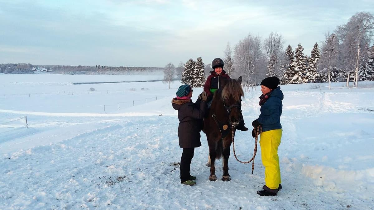 Einari Purra terapiahevosen selässä Torniojokivarressa. Apuna ratsastusterapeutti Lena Lassila, hevosesta huolehtii Jenni Ponkala.