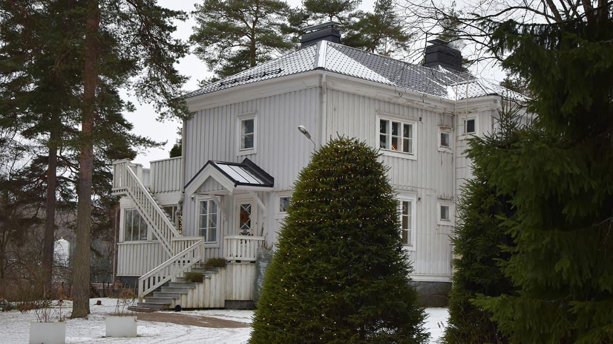 Vaalea, lähes satavuotias lautaverhoiltu kaksikerroksinen talo talvella