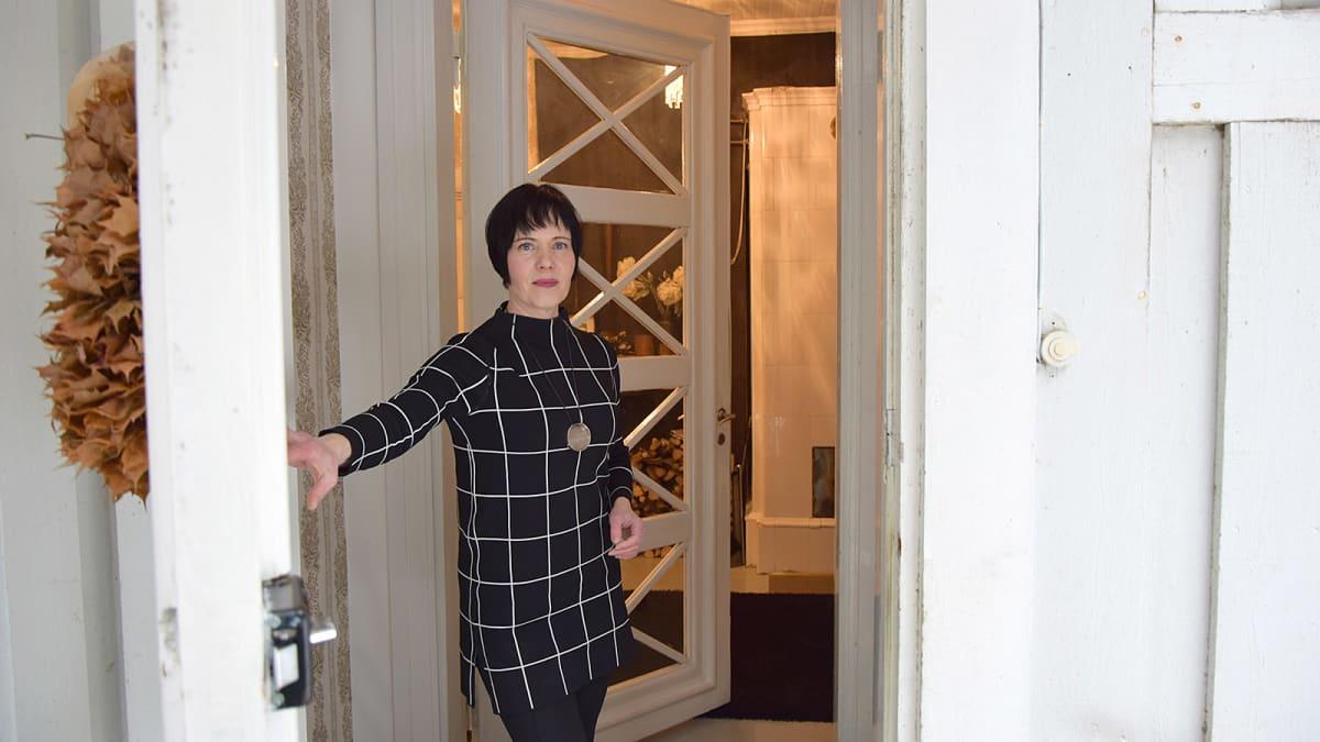 Nainen avaa talon ulko-oven sisäpuolelta