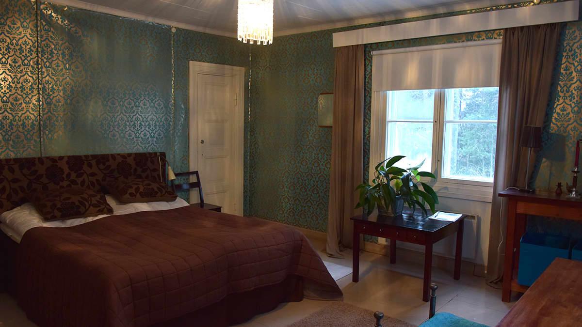 Turkoosin ja ruskean sävyinen huone vahassa talossa