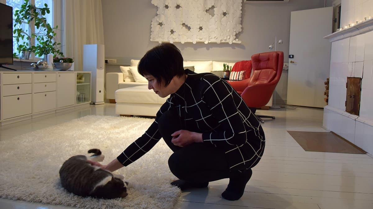 Nainen silittää lattialla makaavaa kissaa olohuoneessa