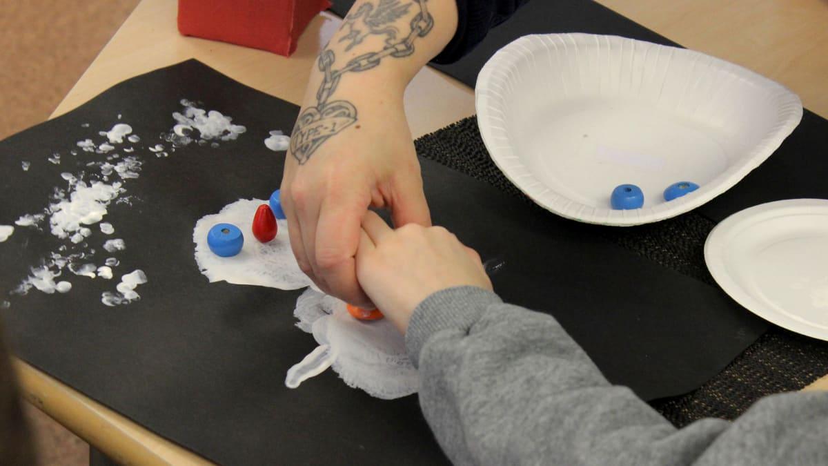 Koulunkäynninohjaaja auttaa oppilasta askartelussa