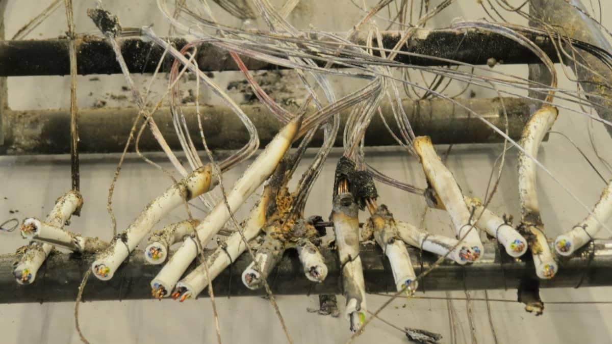 Palaneita sähköjohtoja kaapelitehtaan testauslaboratoriossa