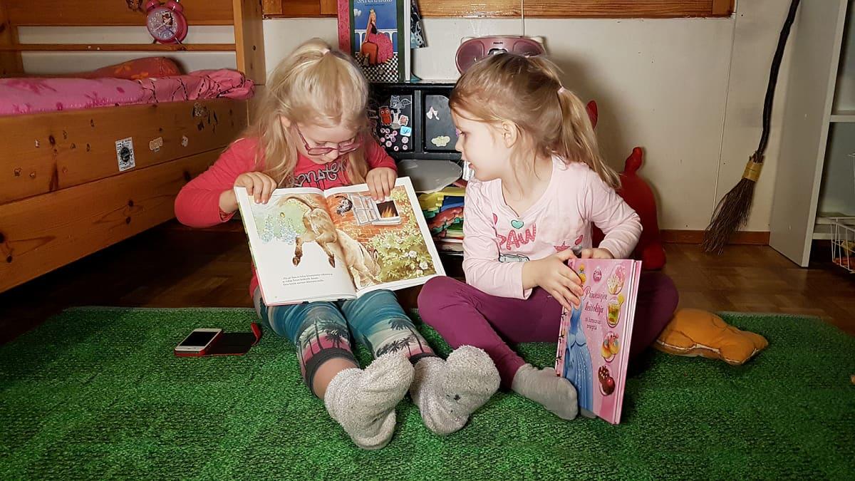 Helmi ja Jade lukevat kirjaa huoneen lattialla.