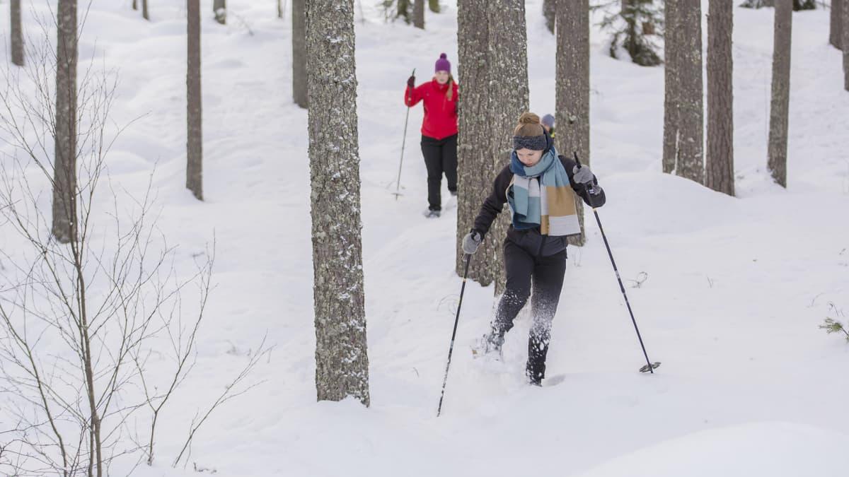 Kaksi naista lumikenkäilee metsässä.