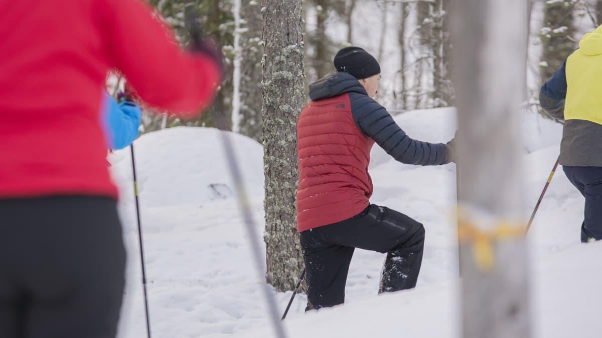 Lumikenkäilijöitä talvisessa metsässä.