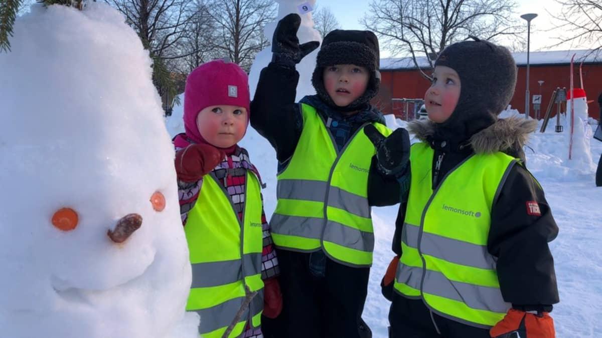 Lapset ihastelevat lumiukkoa.
