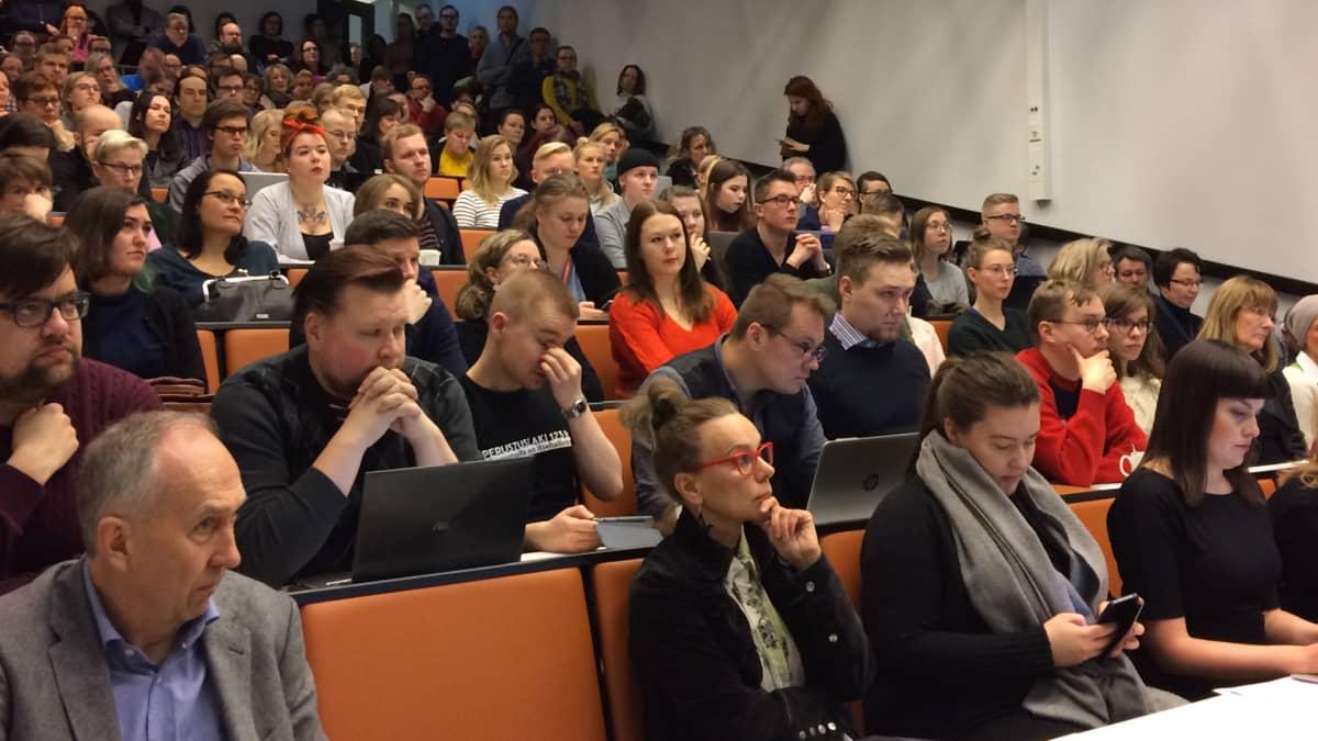 Tampereen yliopiston henkilökunta istuu luentosalissa