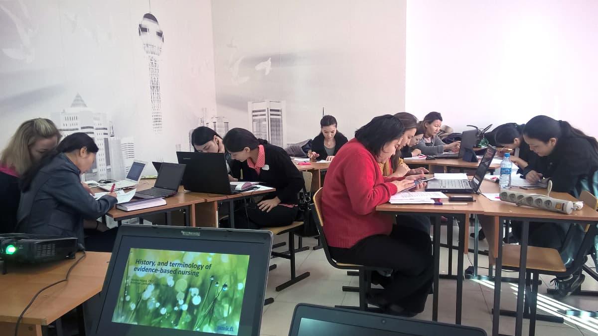 Kazakstanilaiset sairaanhoitajaopiskelijat työskentelevät luokassa.