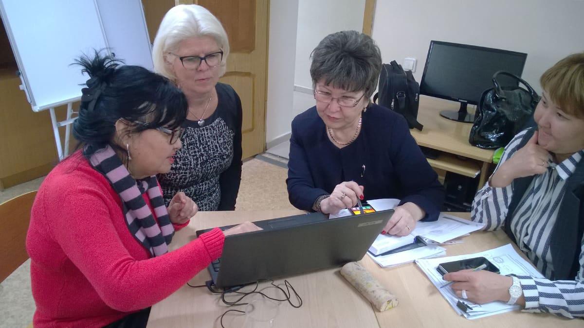 Neljä naista istuu pöydän ääressä ja tekee töitä tietokoneella.