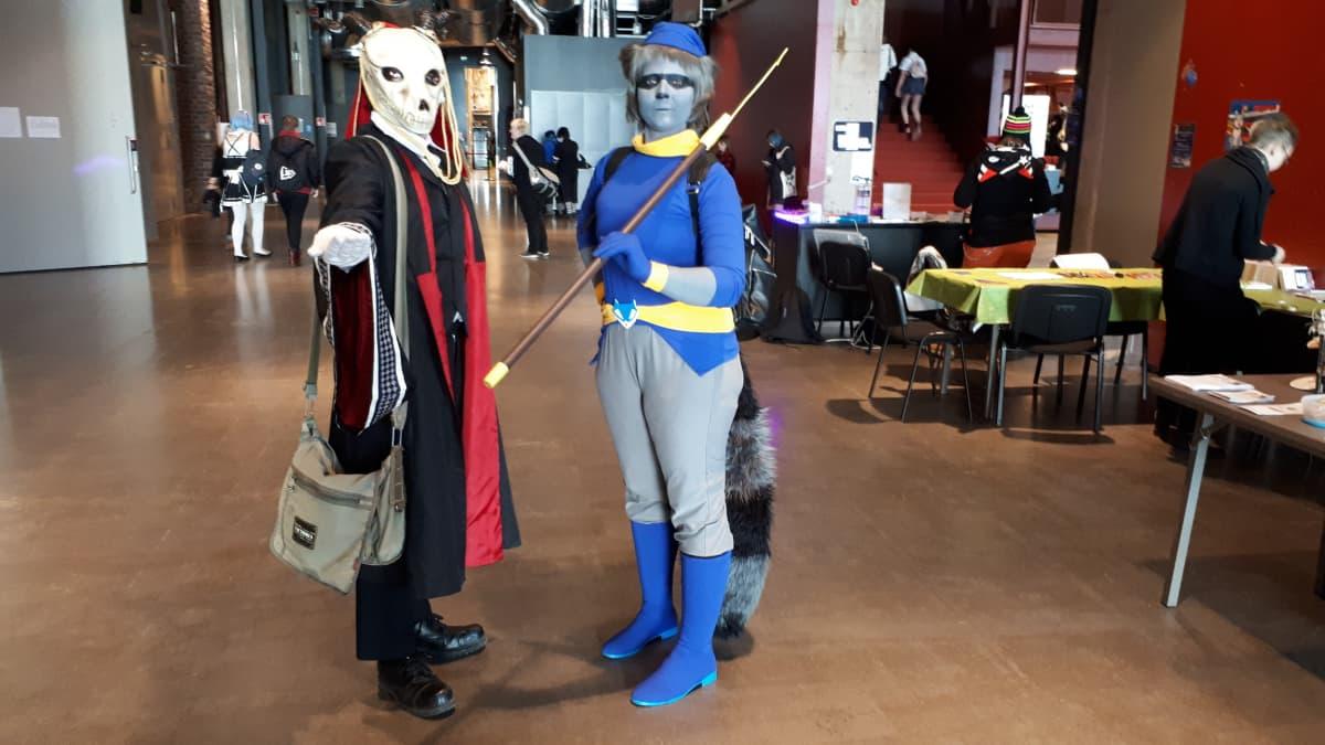 Kaksi pukuilijaa, toisella pässin pääkallon näköinen maski ja toinen on pukeutunut siniseksi pesukarhuksi.