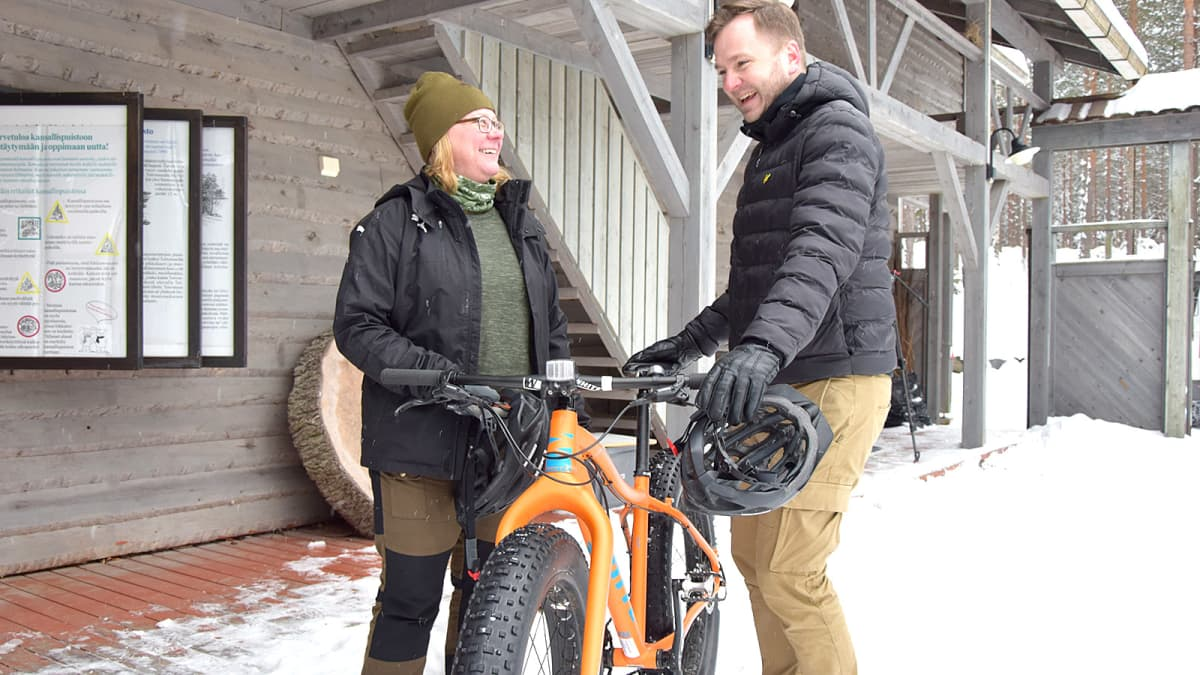 Mies ja nainen juttelevat ulkona talvella välissään fatbike
