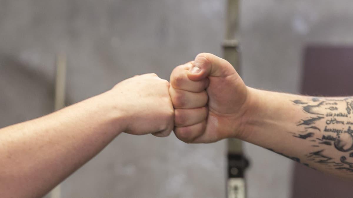 Valmentaja ja valmennettava laittavat nyrkit yhteen.