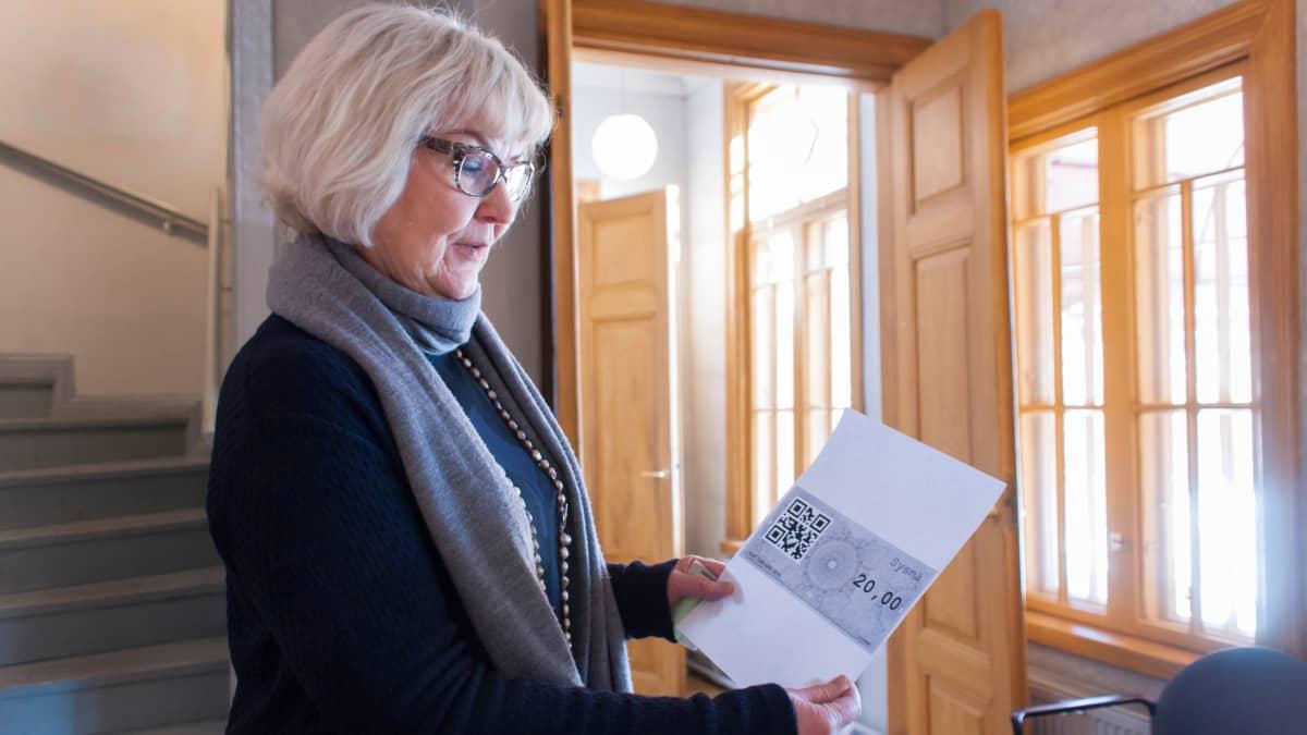 Sysmän kunnanjohtaja Marketta Kitkiöjoki esittelee ensimmäistä ostettua sysmä -valuuttaa.