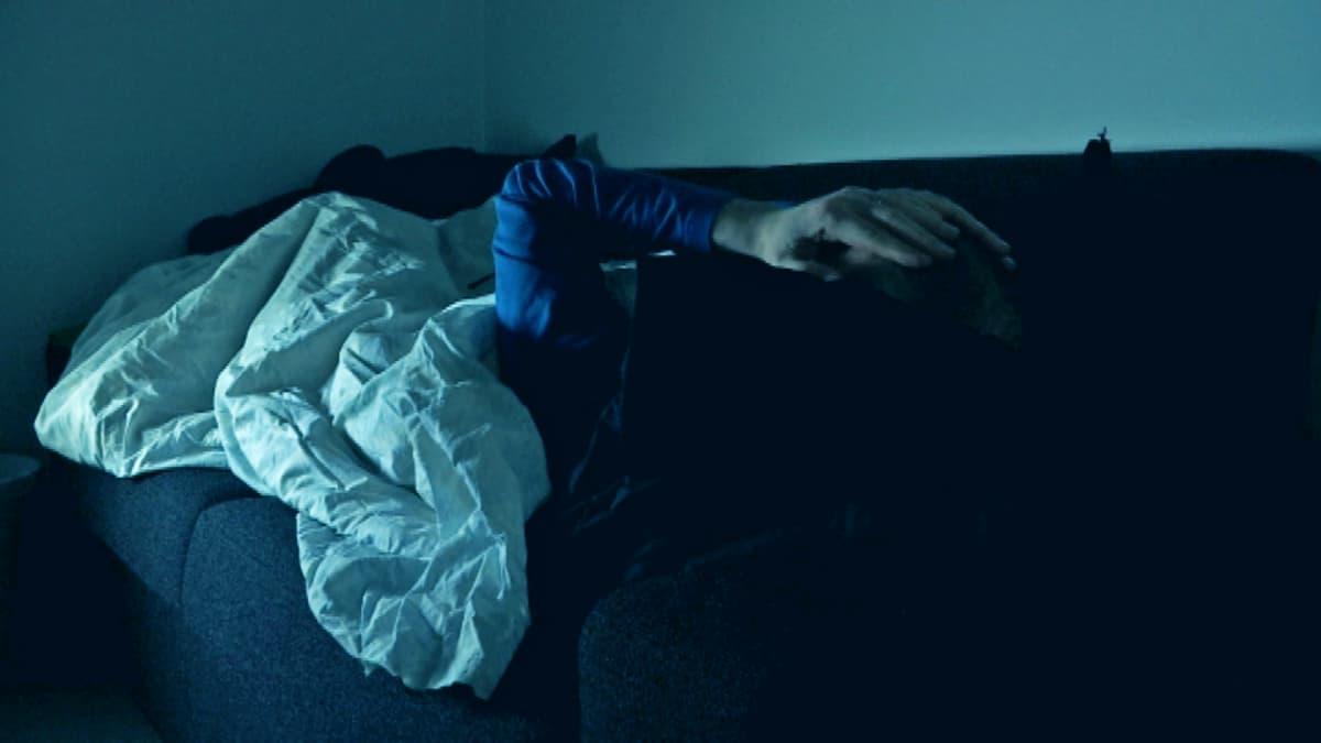 Mies makaa sängyllä ja hieroo kasvojaan väsyneenä