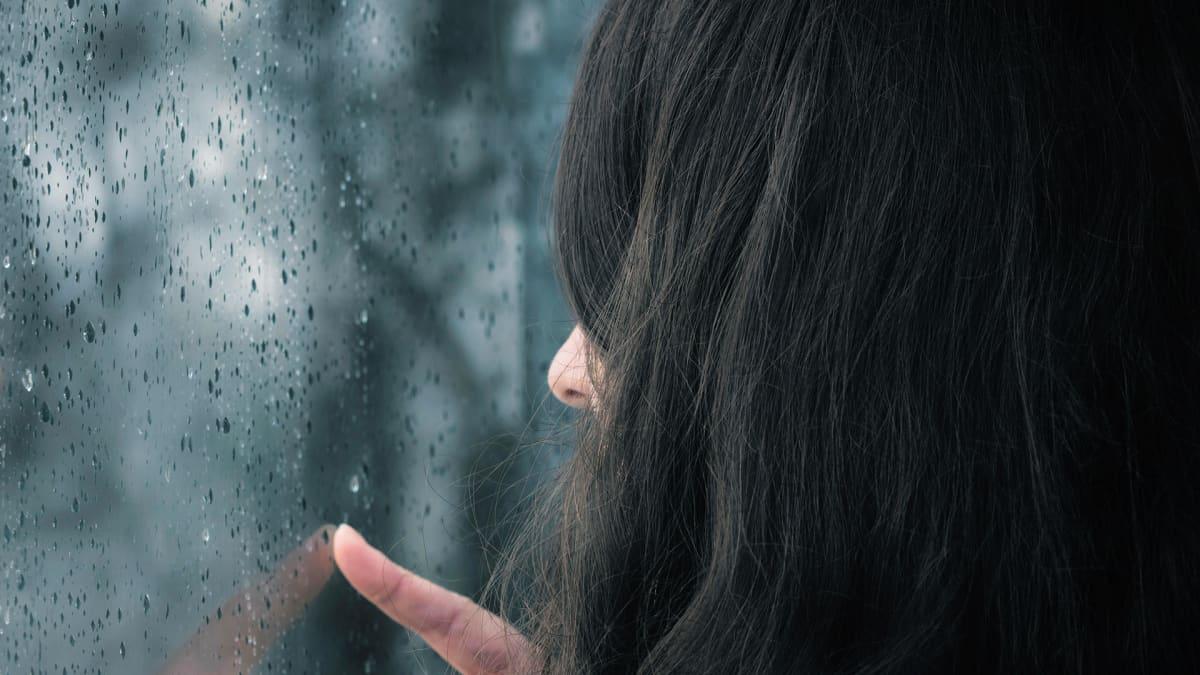 Naine katselee sateisen ikkunan läpi.