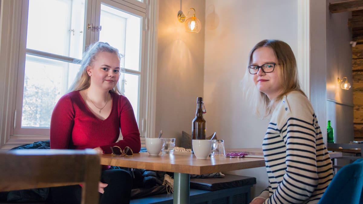 Kaksi nuorta naista istuu ravintolapöydän ääressä.