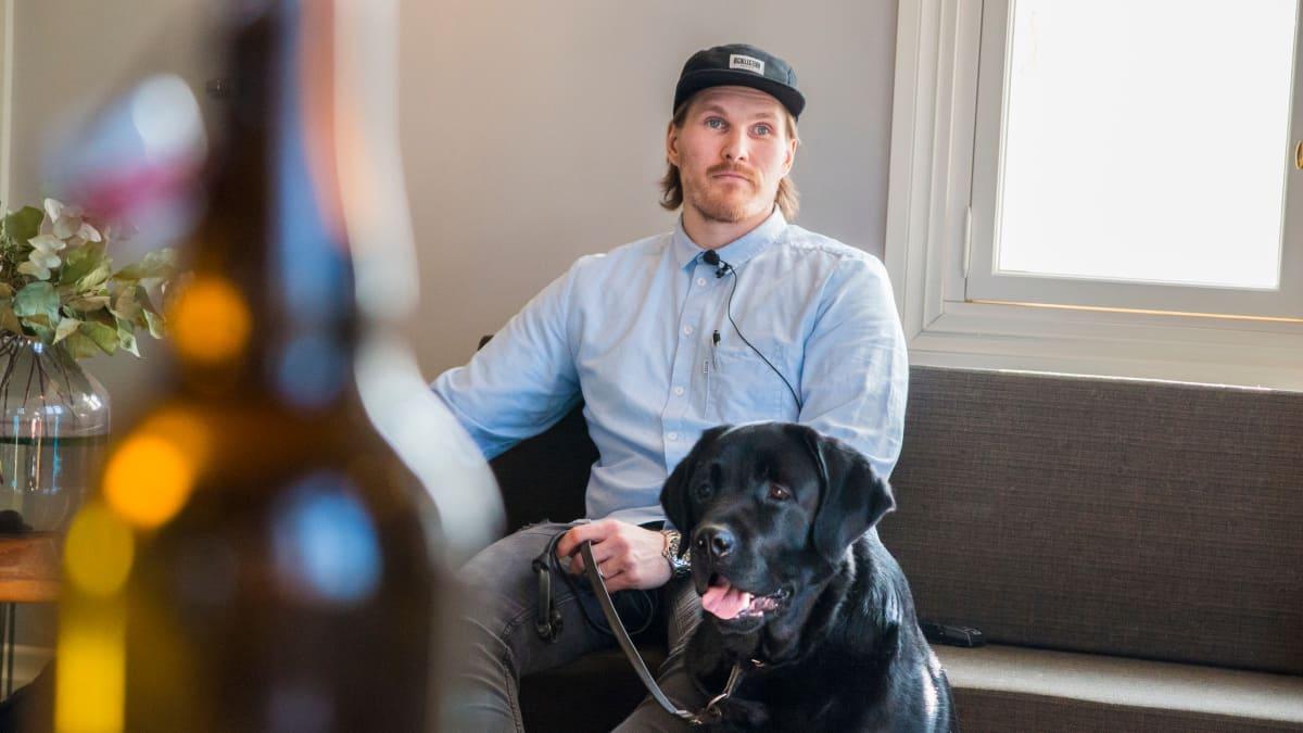 Mies istuu sohvalla vieressään musta labradorinnoutaja.