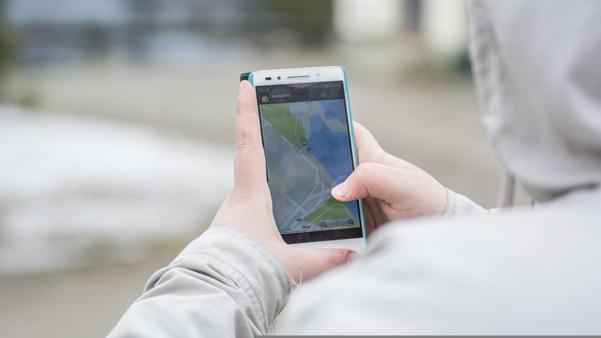 Henkilö navigoi älypuhelimen kartta-sovelluksella.