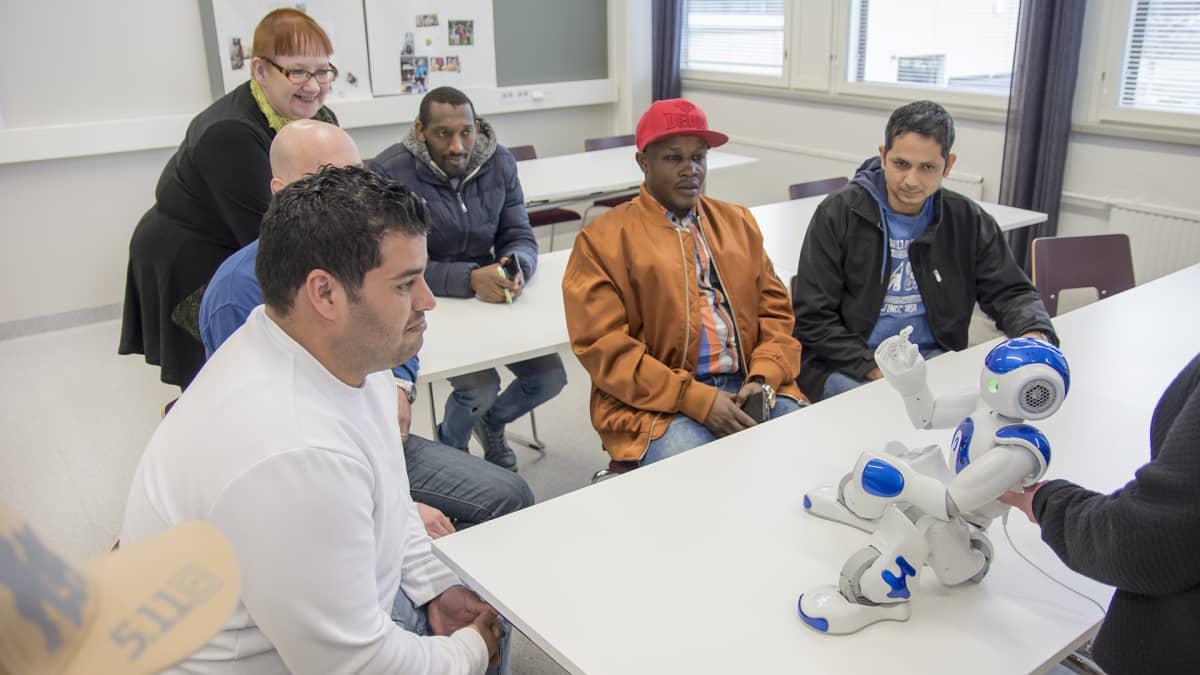 Opiskelijat istuvat humanoidirobotin ympärillä.