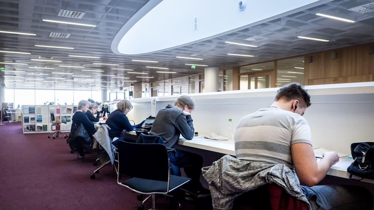 Opiskelijat lukevat kirjastossa