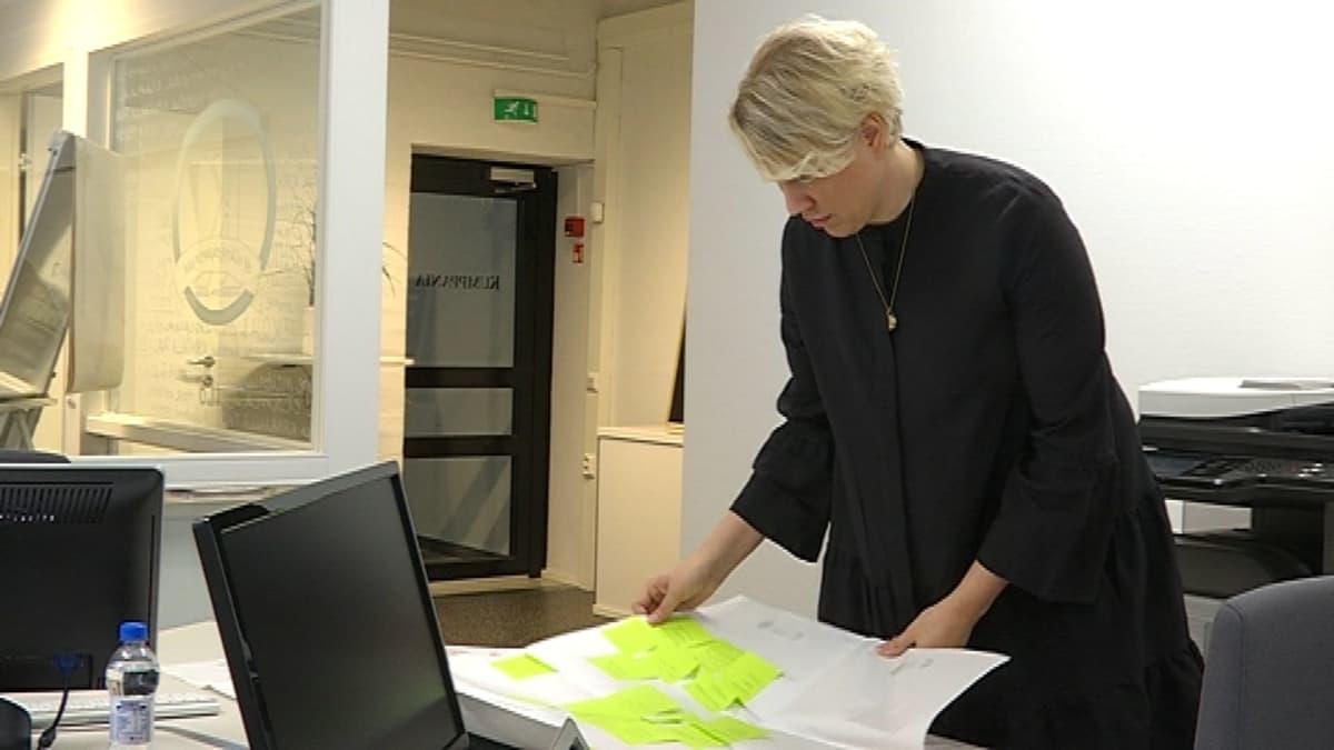 Nainen katsoo pöydällä olevia papereita