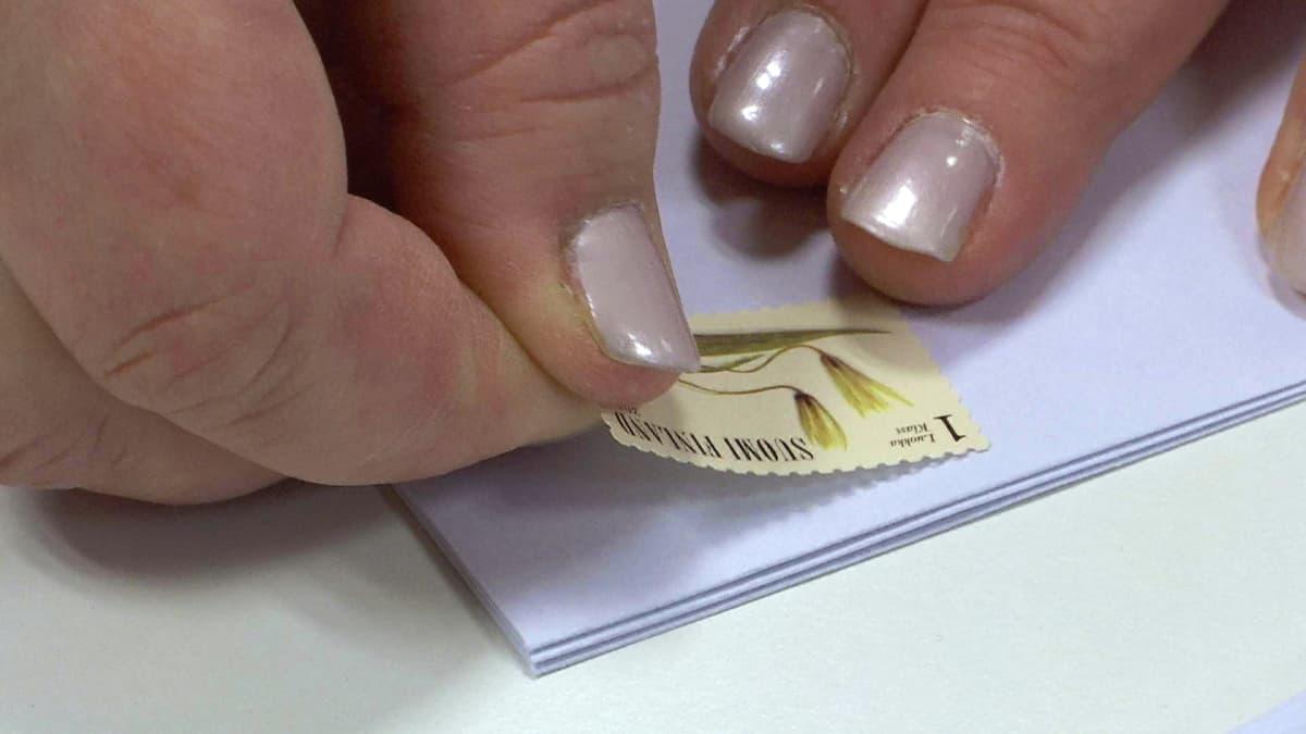 Postimerkki liimataan kirjekuoreen.
