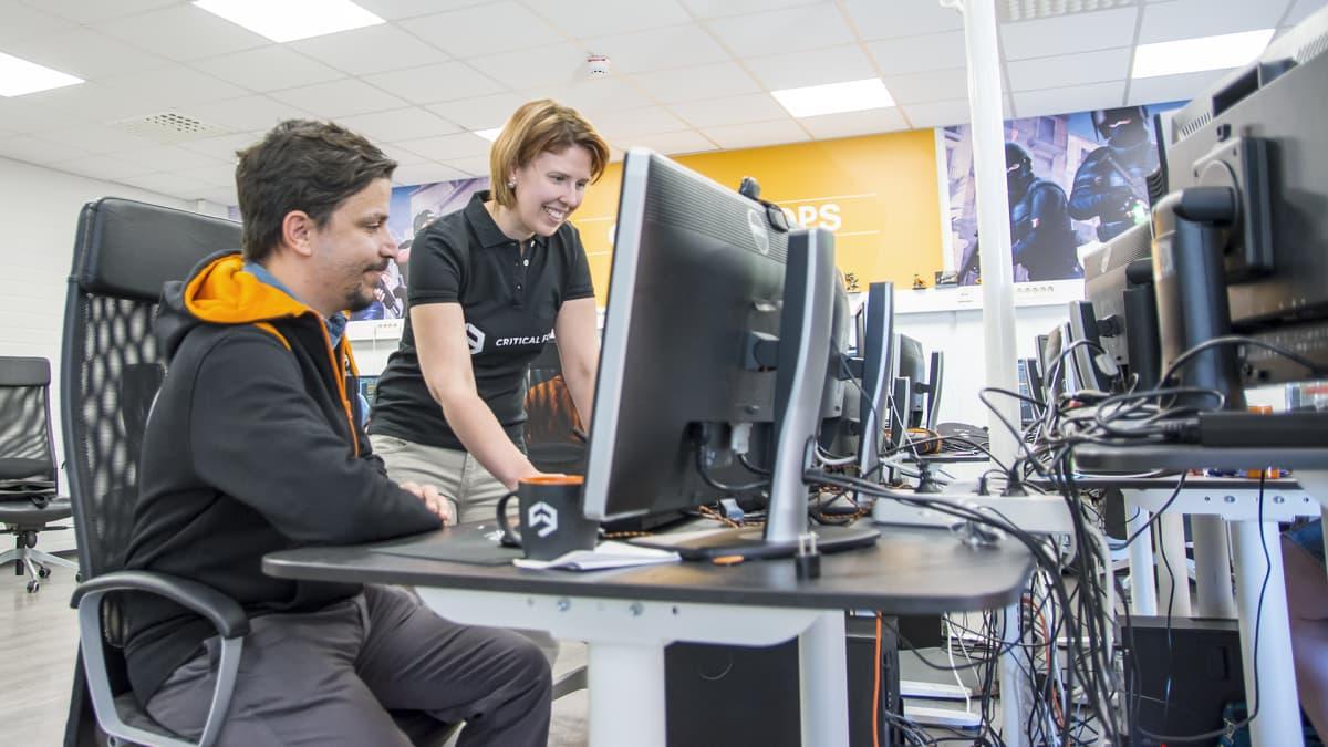 Nainen neuvoo miestä tietokoneen kanssa.
