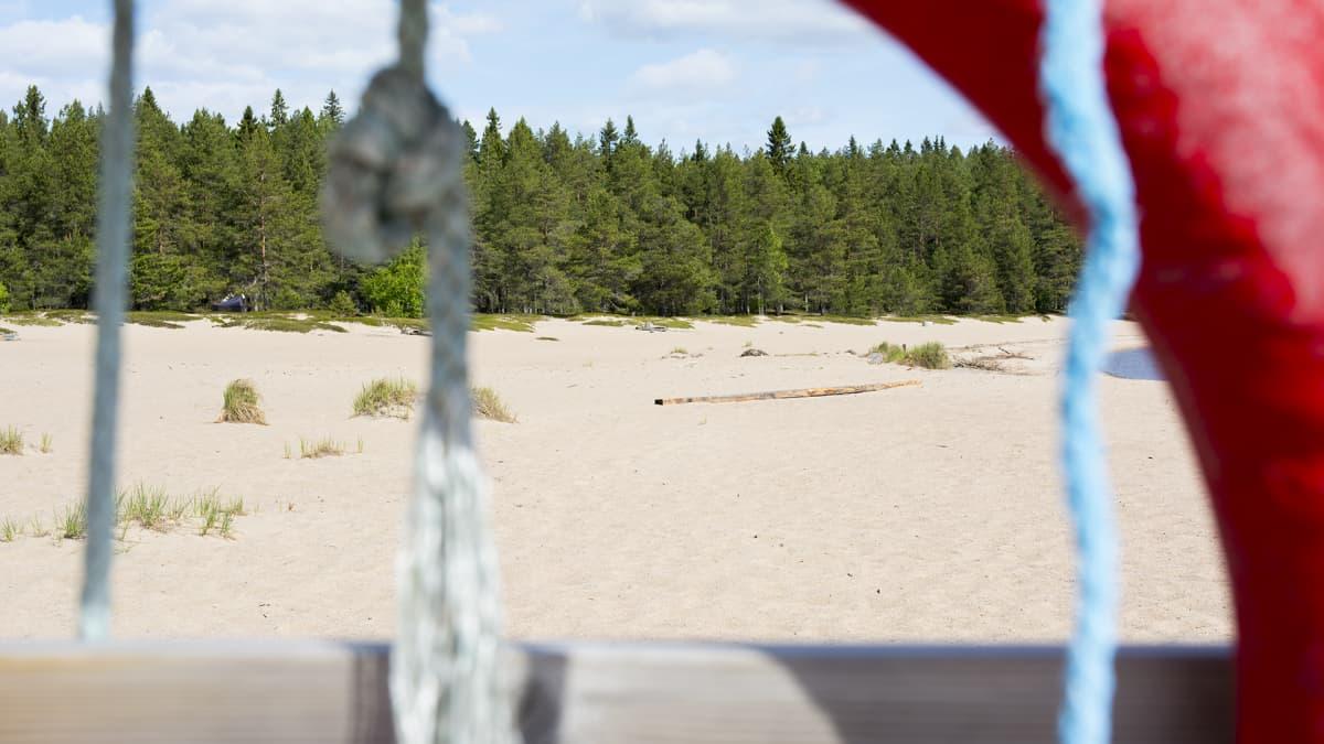 Kuvan etualalla on pelastusrengas ja takana hiekkaranta.
