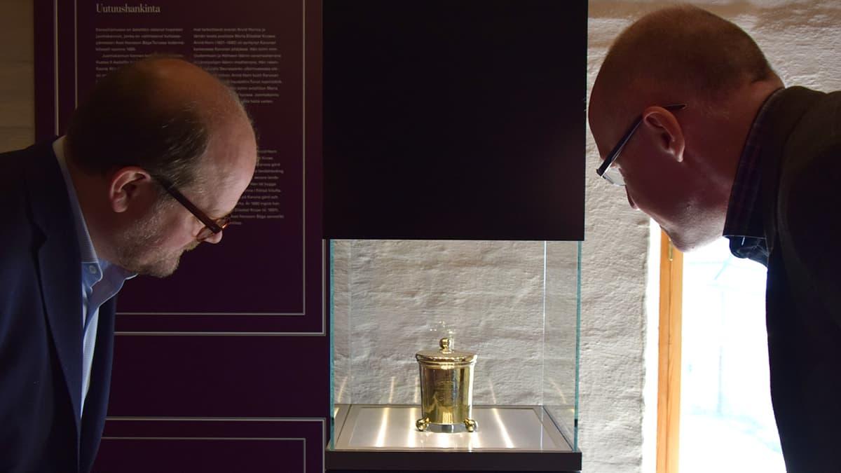 Kaksi miestä katsoo vitriinissä olevaa hopeista juomakannua