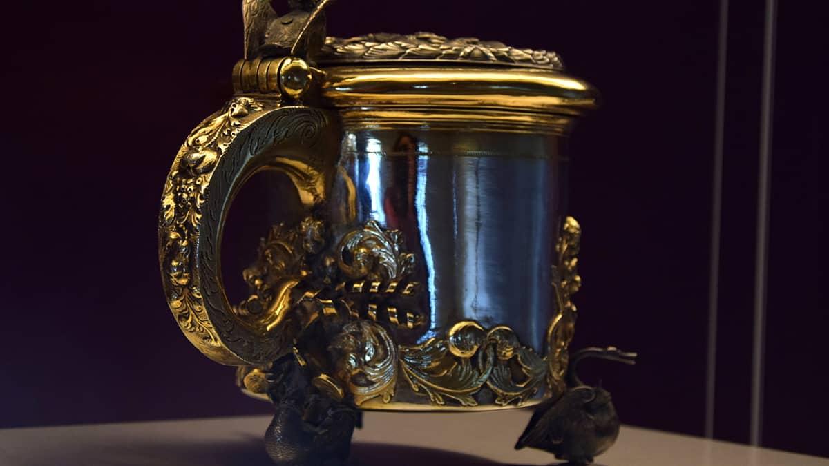 Muhkea hopeinen barokkijuomakannu näyttelyvitriinissä