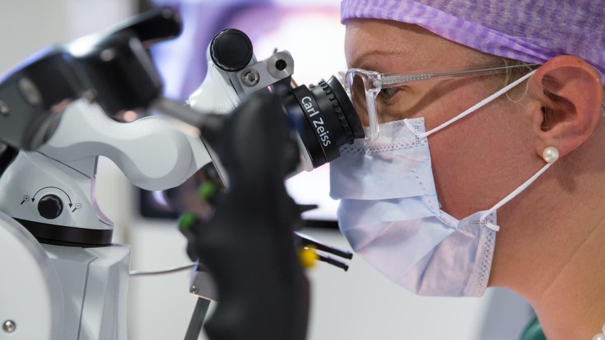 Erikoistuva lääkäri harjoittelee robottimikroskoopin käyttöä
