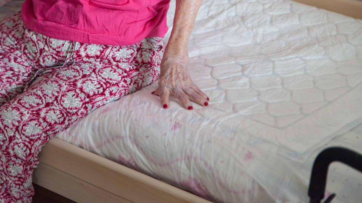 Ikääntynyt nainen istuu sängyllä kuvan vasemmassa laidassa, häntä ei näy kokonaan.