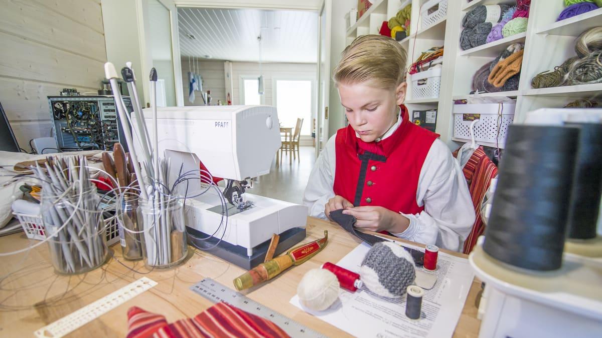 Jaakko Rikalainen ompelee kansallispukua.